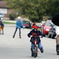 3-year-old Logan Burton looks out for dad, Kelly, right, as 6-year-old Porter (left) and 8-year-old Mykenzie (back) play in the street outside the Burton's home Sept. 25.