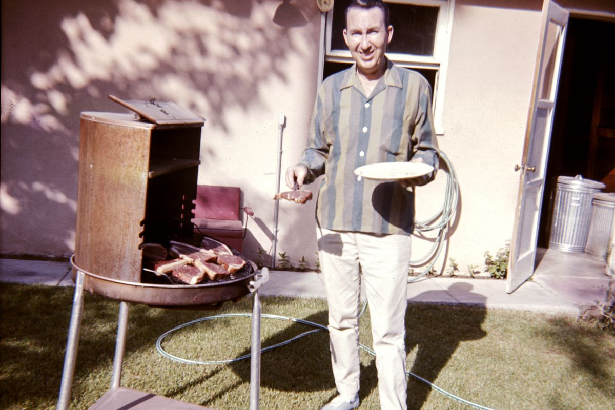 Caucasian man cooking meat on barbecue in yard