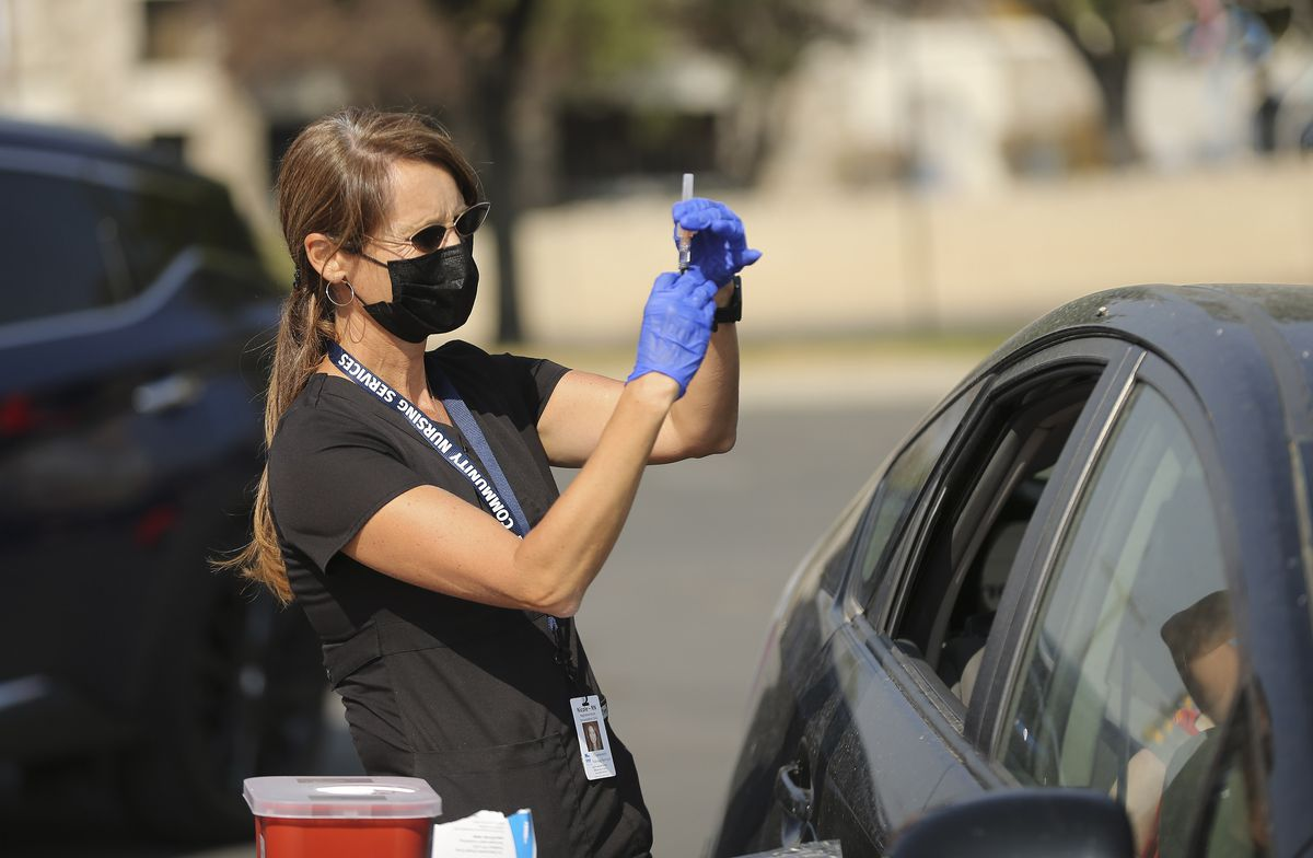 Nicole England, a registered nurse with Community Nursing Services, Nicole England prepares a flu vaccination during a drive through-thru clinic in Salt Lake City on Tuesday, Oct 6, 2020.