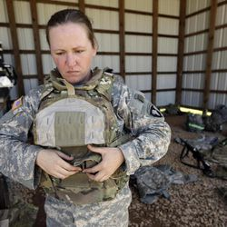 Spec. Sarah Sutphin removes her new body armor after training on a firing range on Tuesday, Sept. 18, 2012, in Fort Campbell, Ky. Female soldiers from 1st Brigade Combat Team, 101st Airborne Division are field testing the first Army body armor designed to fit women's physiques in preparation for their deployment to Afghanistan this fall.