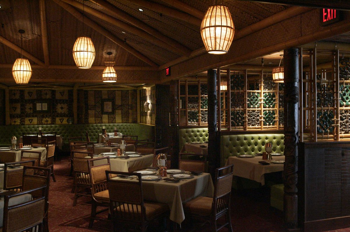 Dining room with green booths, tablecloth-topped tables, and wood lanterns hanging from ceiling.
