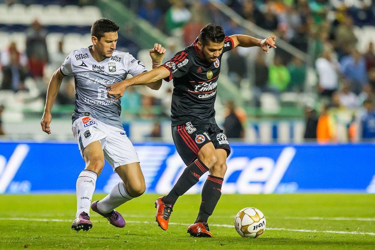 Tijuana's Henry Martín fights for a ball against León's Guillermo Burdisso in the 2016 Apertura Liguilla Quarterfinal.