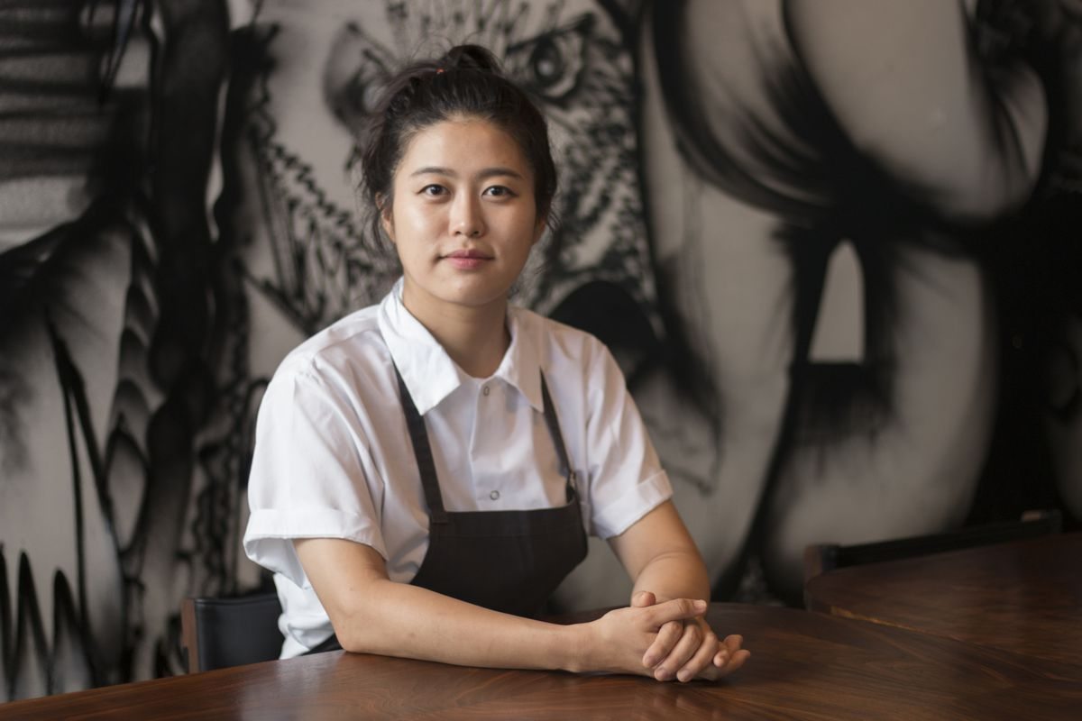A portrait photo of chef Eunjo Park in a white collared shirt and apron, sitting at a table with her hands clasped in front of her.
