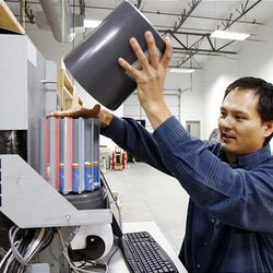 Lanner Fayad, of uGenius, places a coin dispenser on the back of a video banking machine.