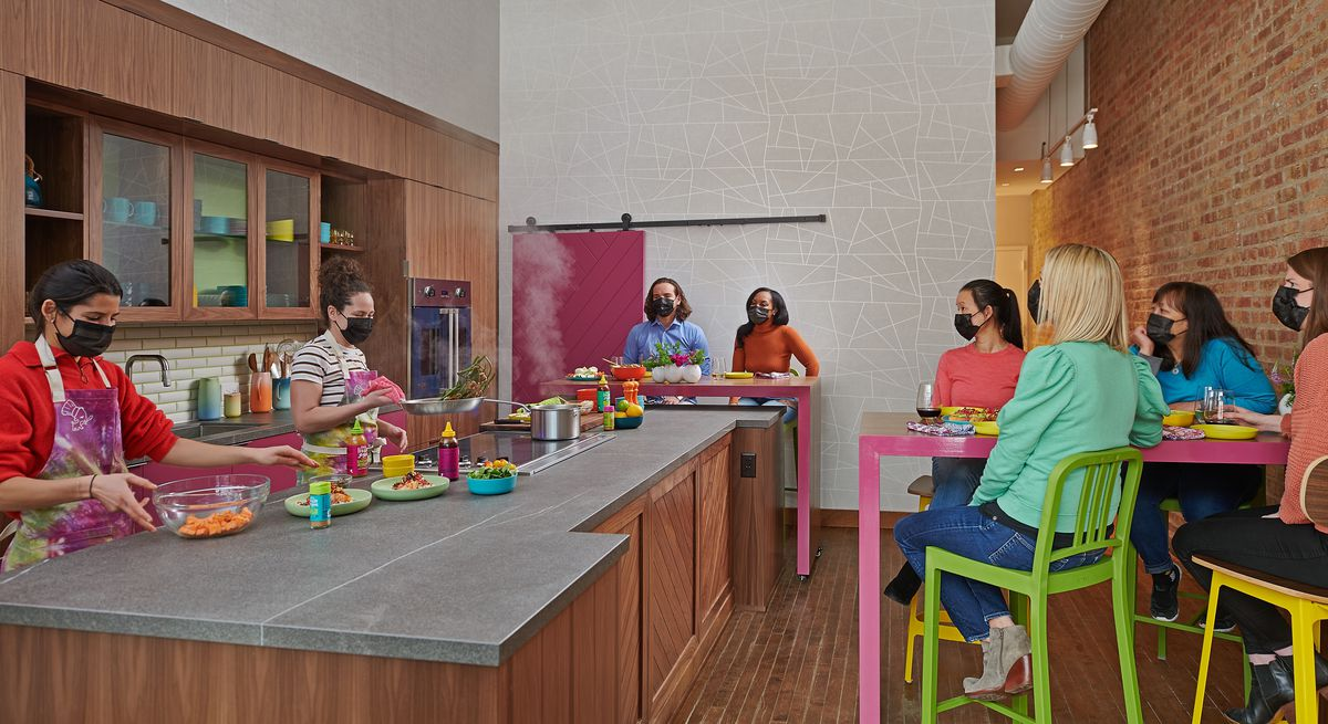 A group of women in masks are seated at high-top tables around a small test kitchen. They are looking at Stephanie Izard, a female chef in a striped shirt wearing a black mask.