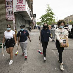 Community volunteers with brooms, dust pans and garbage bags walk to help store owners clean up, Tuesday, June 2, 2020, in the Fordham Road area of the Bronx borough of New York. Protesters broke into stores Monday night in reaction to George Floyd's death while in police custody on May 25 in Minneapolis.
