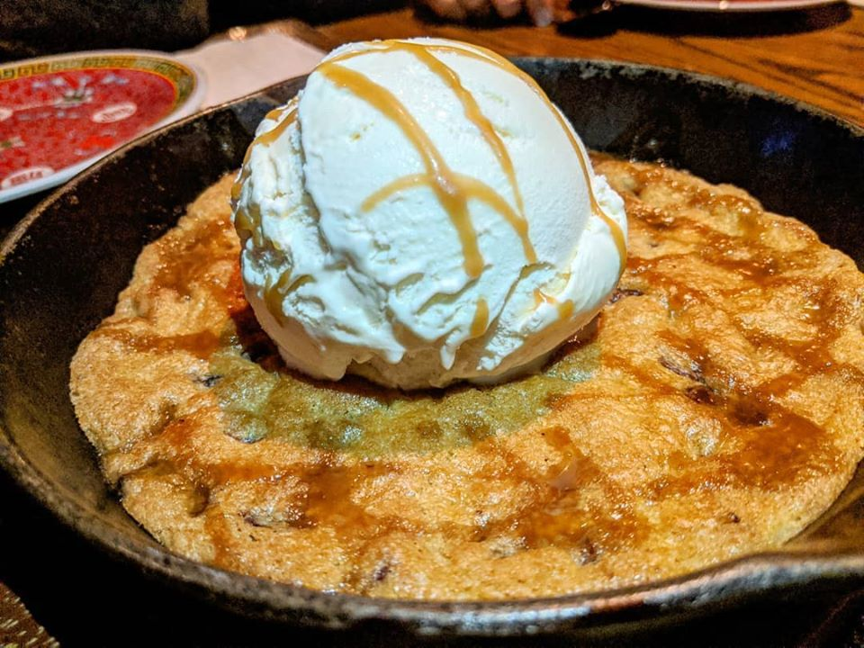 A cookie served in a cast-iron skillet is topped with a scoop of ice cream and drizzled with caramel