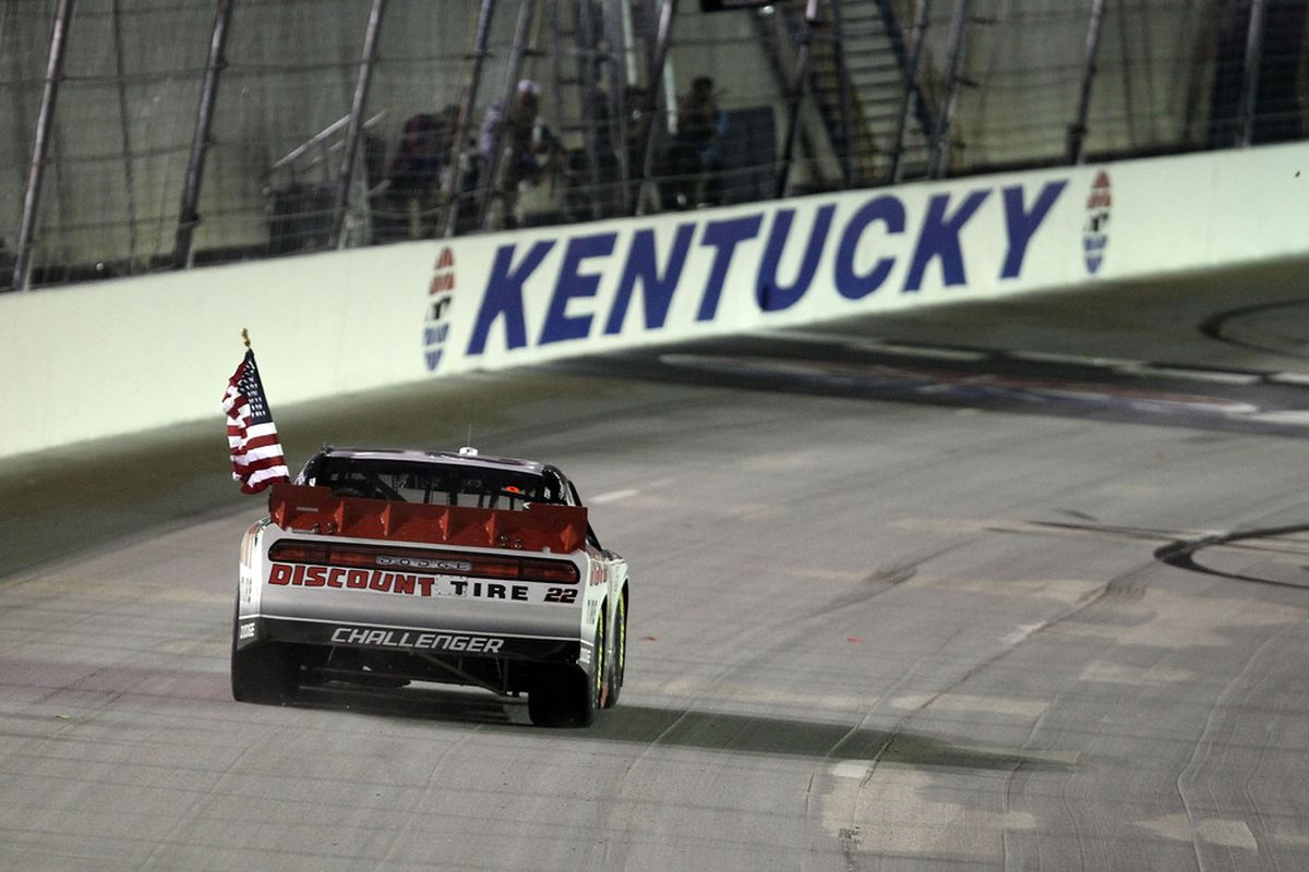Brad Keselowski celebrates with the checkered flag after winning the NASCAR Nationwide Series Feed the Children 300 at Kentucky Speedway.