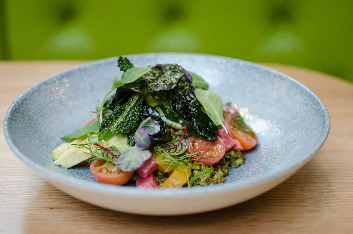 A simple salad is in a pale blue bowl on a wooden table, with a green booth visible in the background.