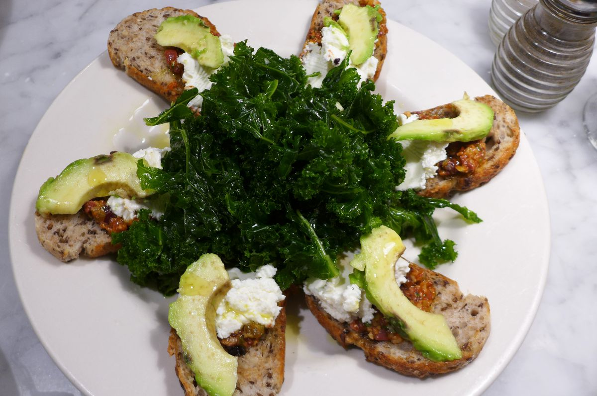 toasts topped with avocado radiate from a kale salad in the middle...
