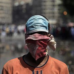 An Egyptian protester with covers his face during clashes with security forces, not shown, near the U.S. embassy in Cairo, Egypt, Friday, Sept. 14, 2012. The protests are part of widespread anger across the Muslim world about a film ridiculing Islam's Prophet Muhammad.