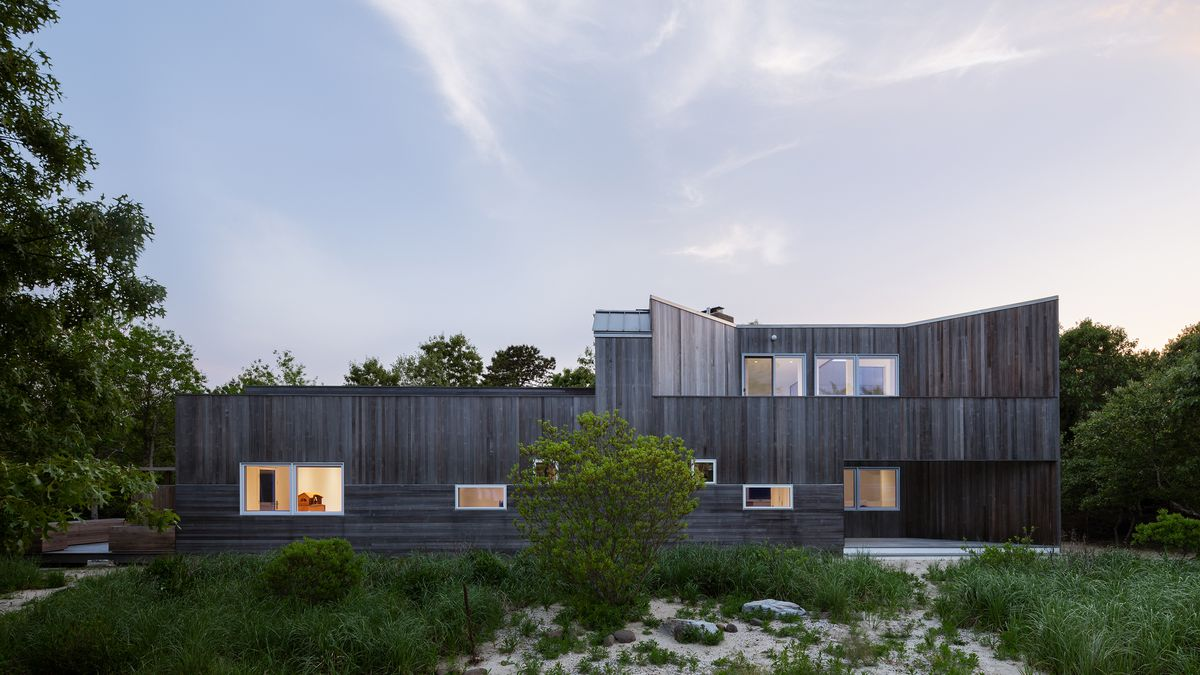 A two-story cedar-clad house sits among trees on a sand dune. There are rectangular windows positioned irregularly on the facade.