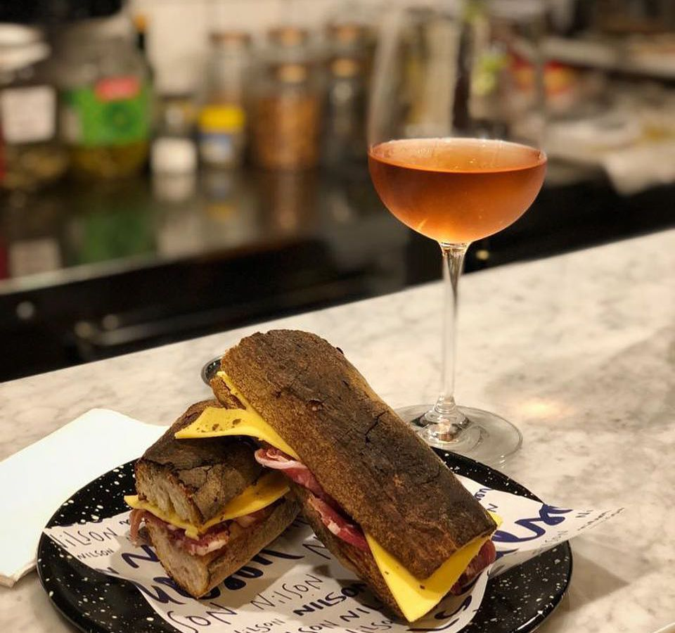 A baguette sandwich sliced in half with cheese and deli meat visible from the side, alongside a glass of rose wine on a marble counter