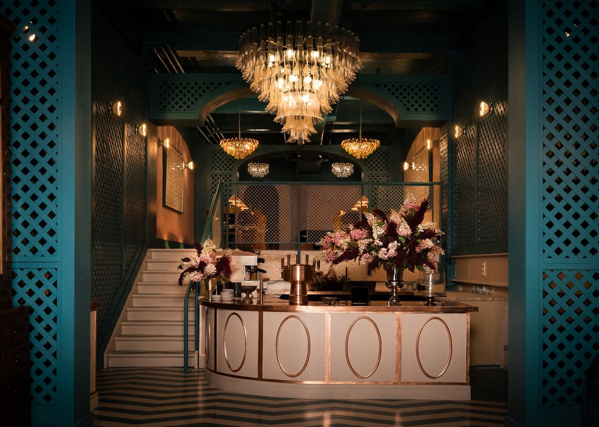 The interior of a luxe cafe, with three chandeliers visible in the foreground and background