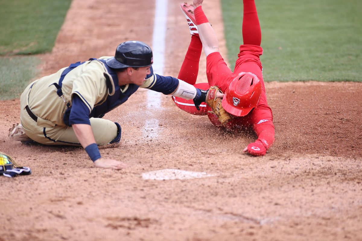 Georgia Tech catcher tags NC State baserunner out at the plate.