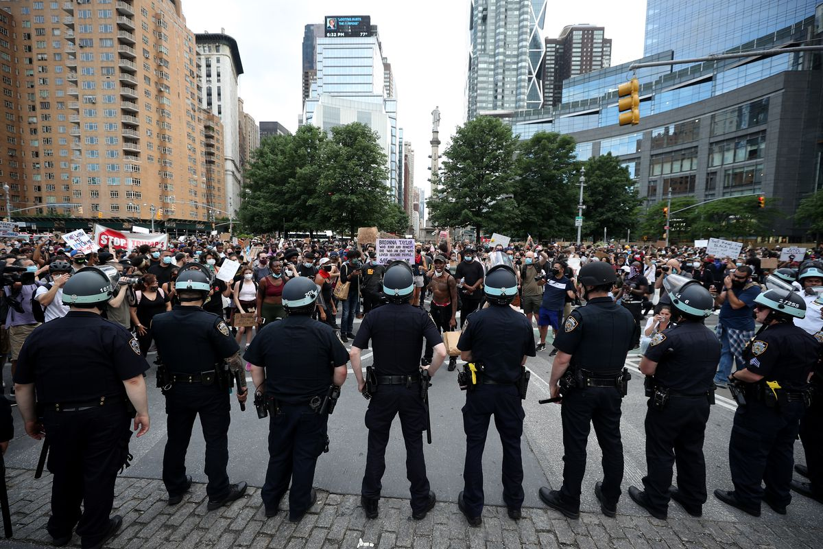 A row of police officers stand in front of protesters.