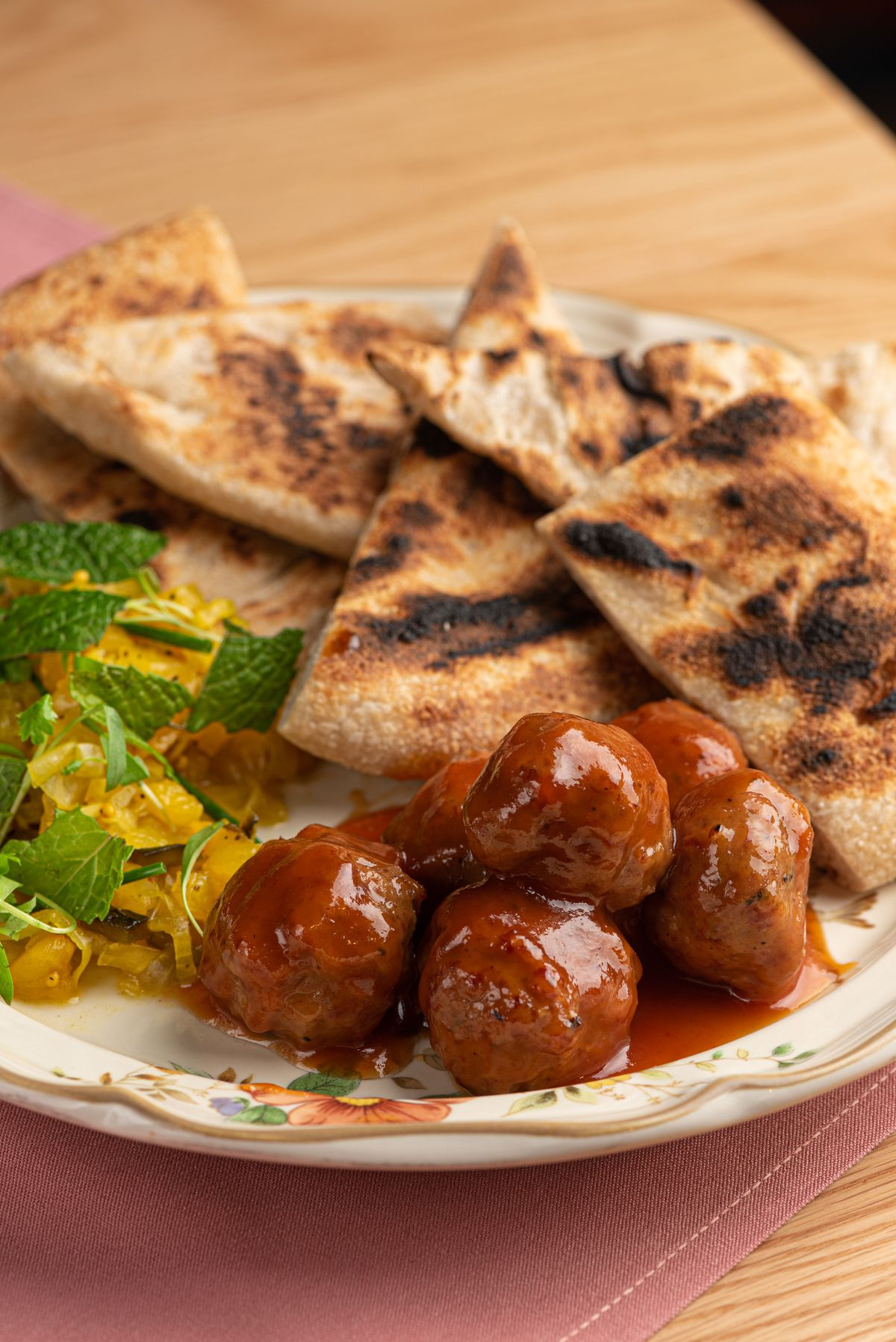 Small glazed brown bites of ham with blistered flatbread around the sides.