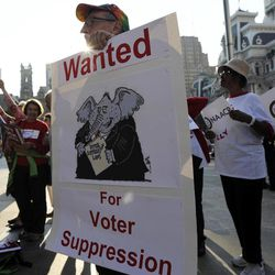 Joe Michetti holds a sign to demonstrate the opposition of Pennsylvania's new voter identification law during the NAACP voter ID rally, Thursday, Sept. 13, 2012, in Philadelphia. Pennsylvania's Supreme Court justices are scheduled to hear arguments over whether a new law requiring each voter to show valid photo identification poses an unnecessary threat to the right to vote.