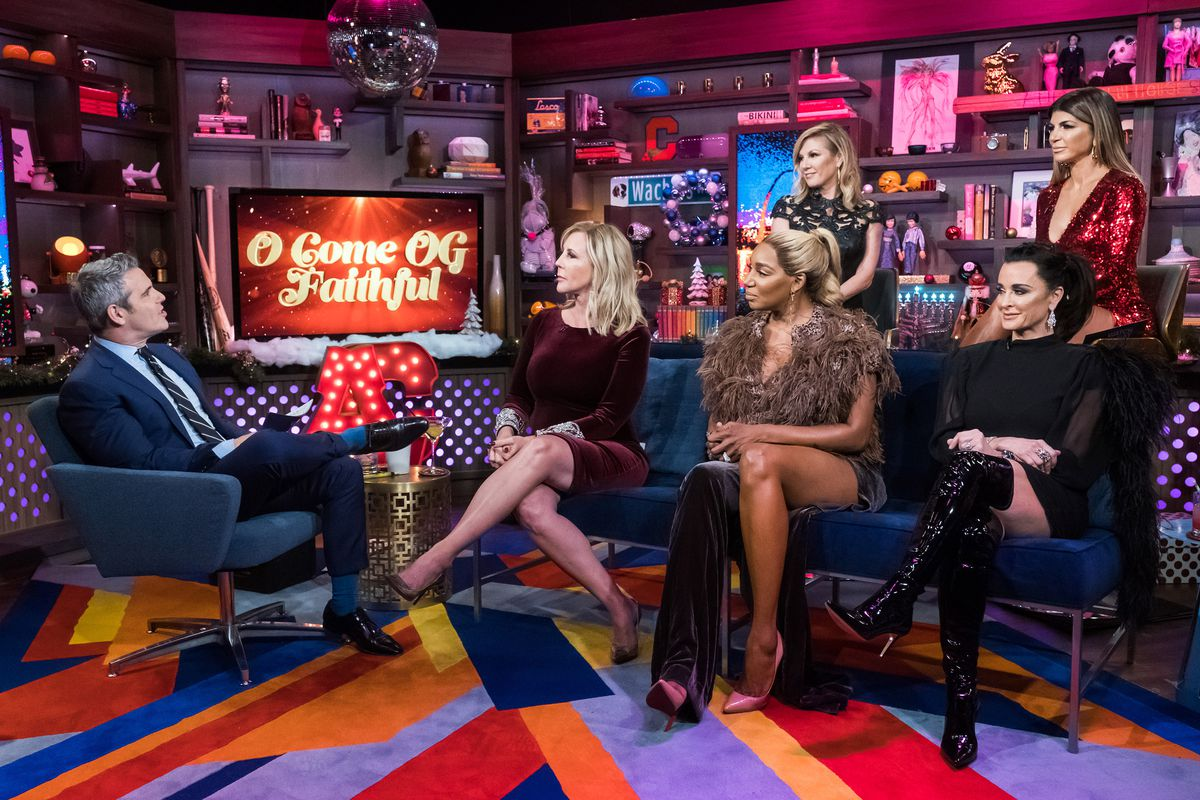 """Five women from the show """"The Real Housewives"""" sit in two tiers of seats on a stage facing the host of the show """"Watch What Happens Live."""""""