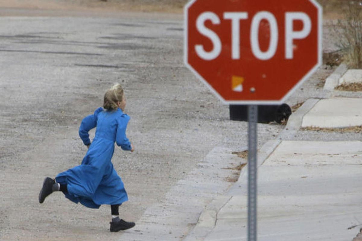FILE - In this Dec. 16, 2014, file photo, a girl runs past a street sign in Hildale, Utah. Federal prosecutors plan to bring a mix of law enforcement leaders and ex-sect members to a hearing in which they'll ask a judge to disband the police department in