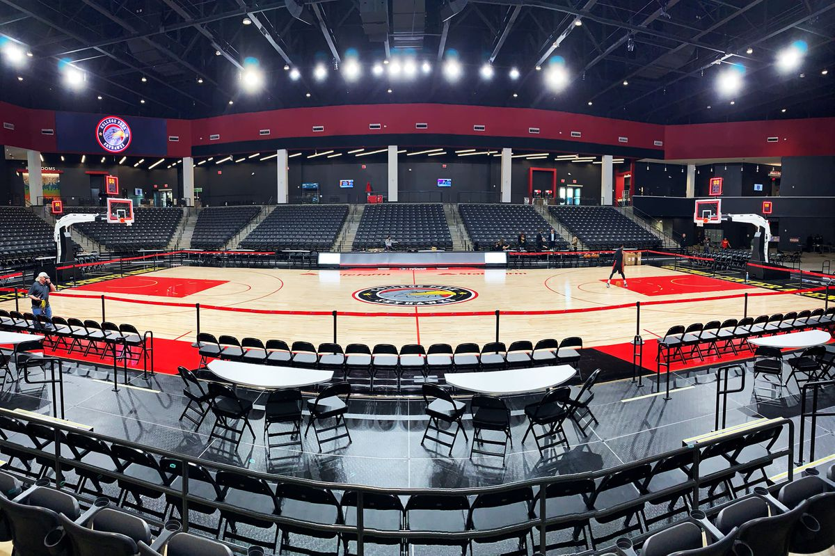 Interior of arena set up with a basketball court and bleacher seats.