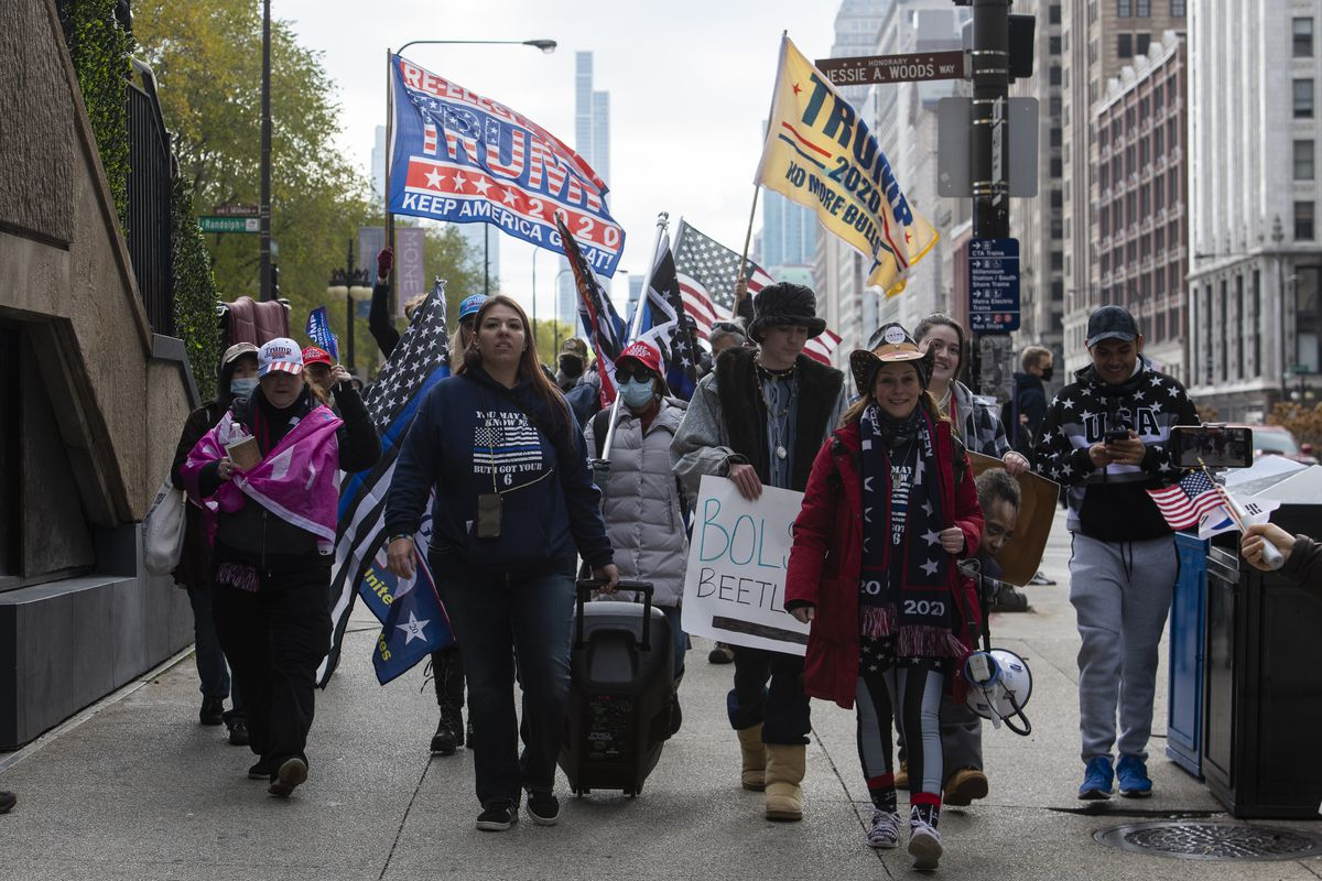 """A group of """"stop the steal"""" protesters walk toward Trump Tower after protesting in Millennium Park, Thursday, Nov. 26, 2020."""