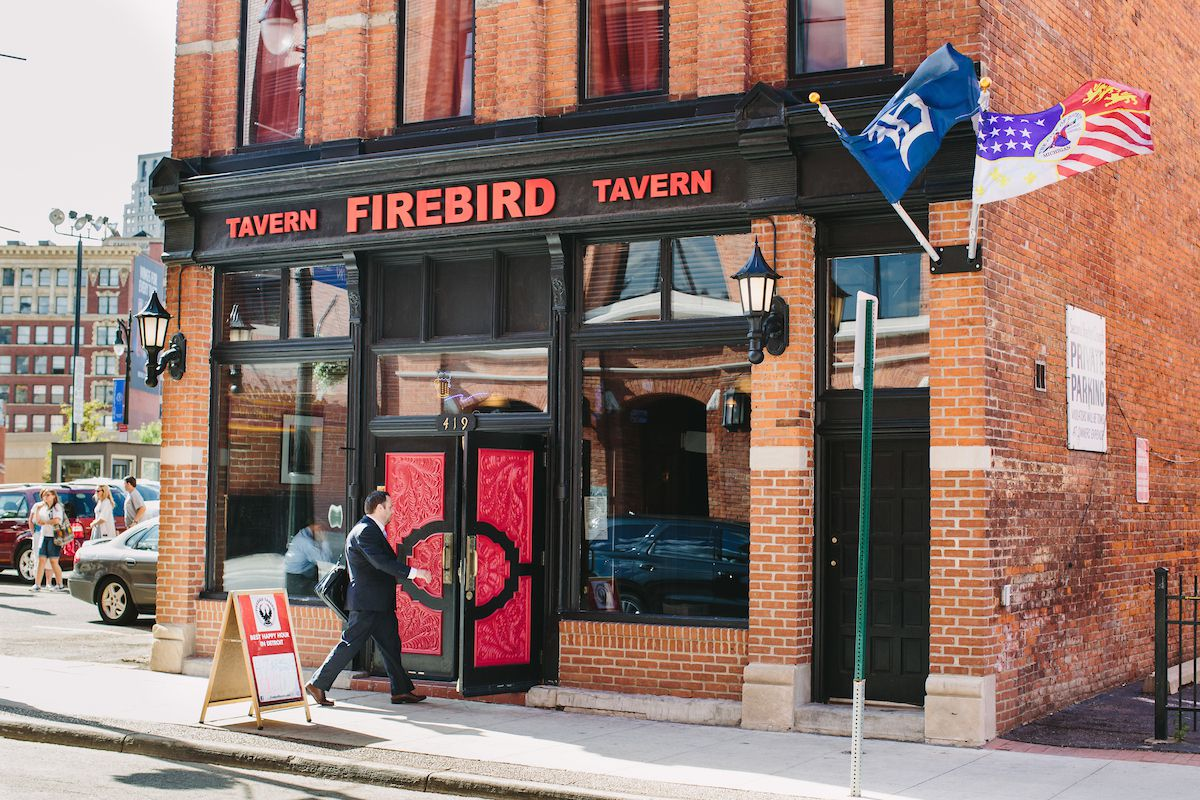 A man walks through the Firebird Tavern's red and black on a winter day with snow still patchy on the ground.