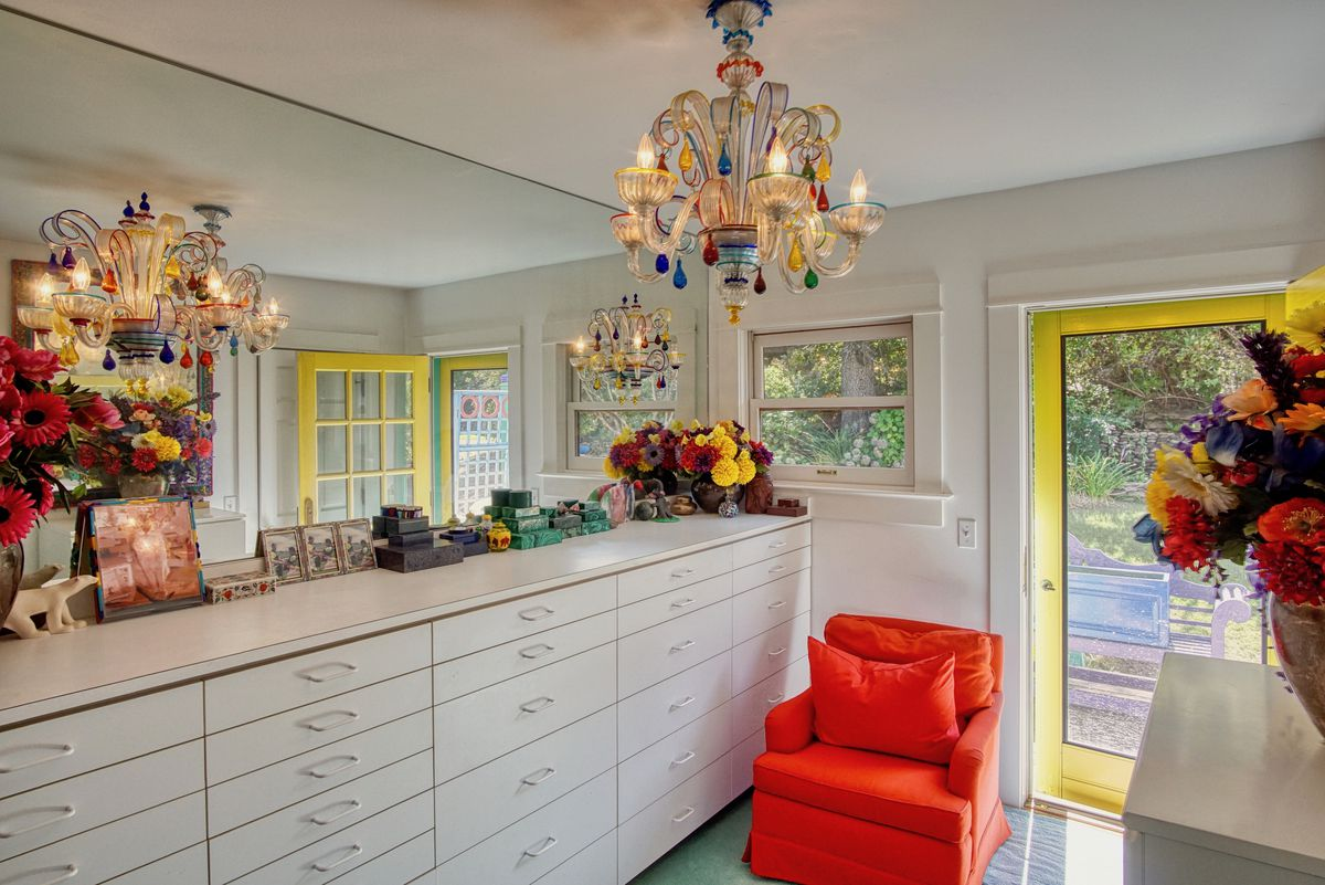 A closet area with white drawers, an orange chair, large mirror, and chandelier.