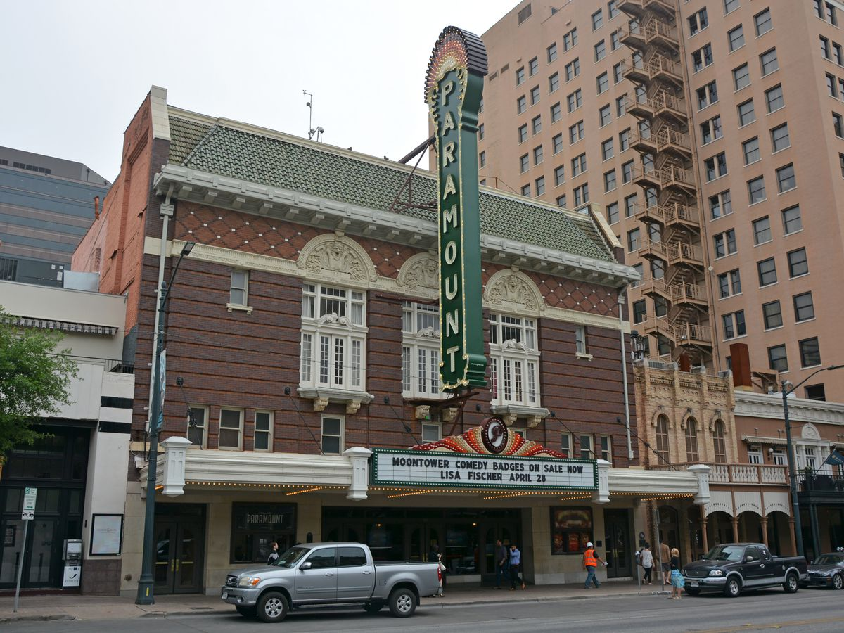 """Red brick old theater with neon blade/ vertical front sign that says """"Paramount Theatre"""""""