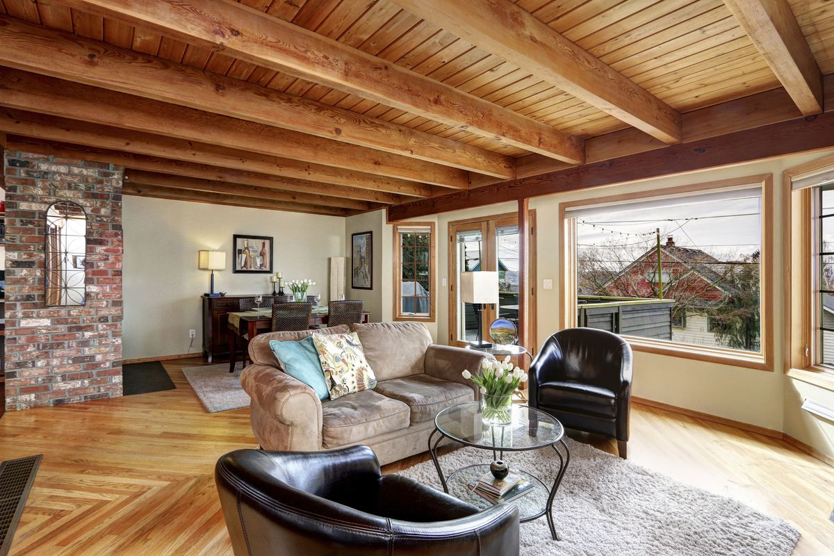 A living area with an exposed wood ceiling, chevron hardwood flooring, and large windows