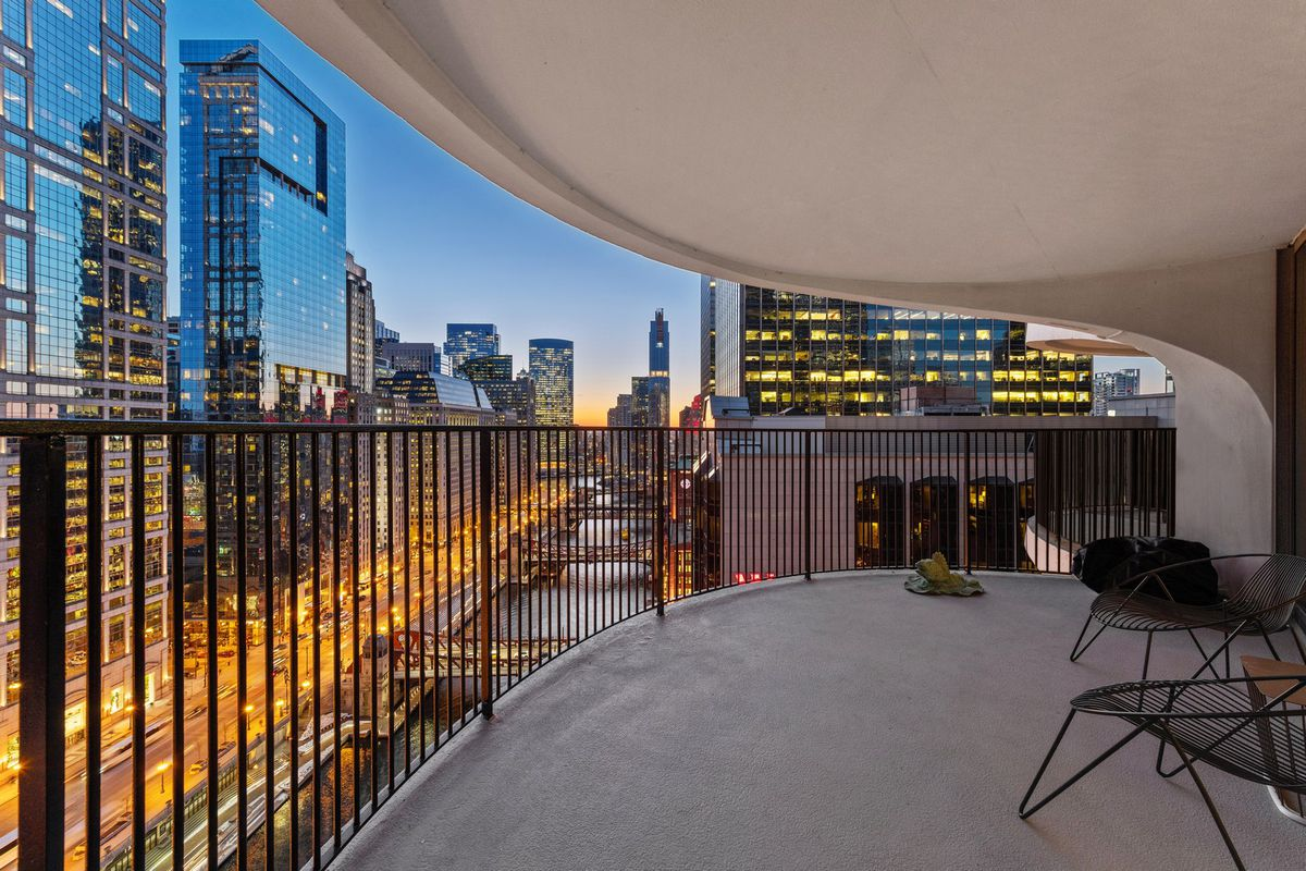 A skyscape at dusk can be seen from an elevated balcony with a curving metal rail and two outdoor chairs.