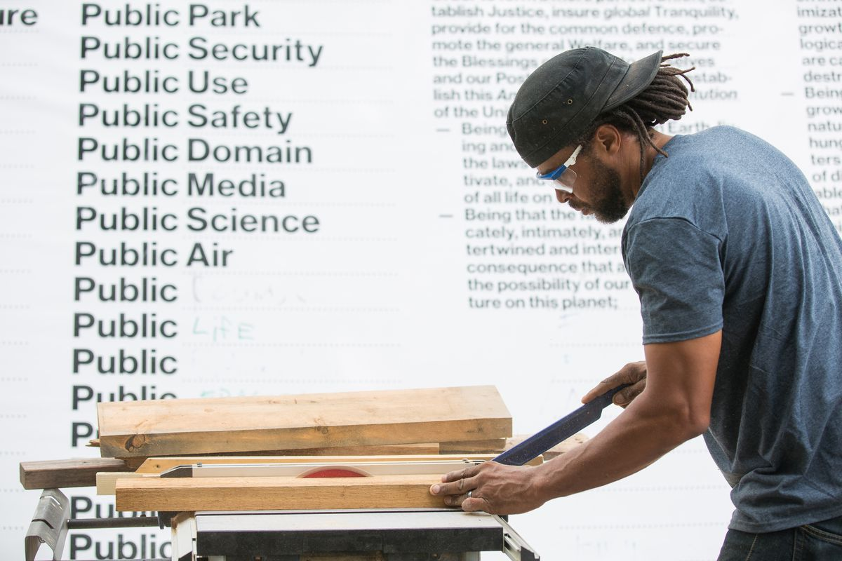 An African-American man in a t-shirt and protective glasses uses a chisel on pieces of lumber.