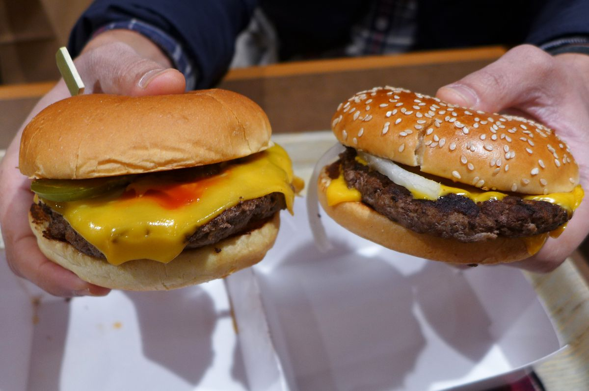 Two hands hold two cheeseburgers, one with seeds on the bun, the other without.