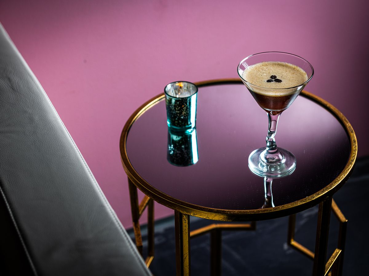 Espresso martini next to a couch on an art deco-style table with another drink to the side of it