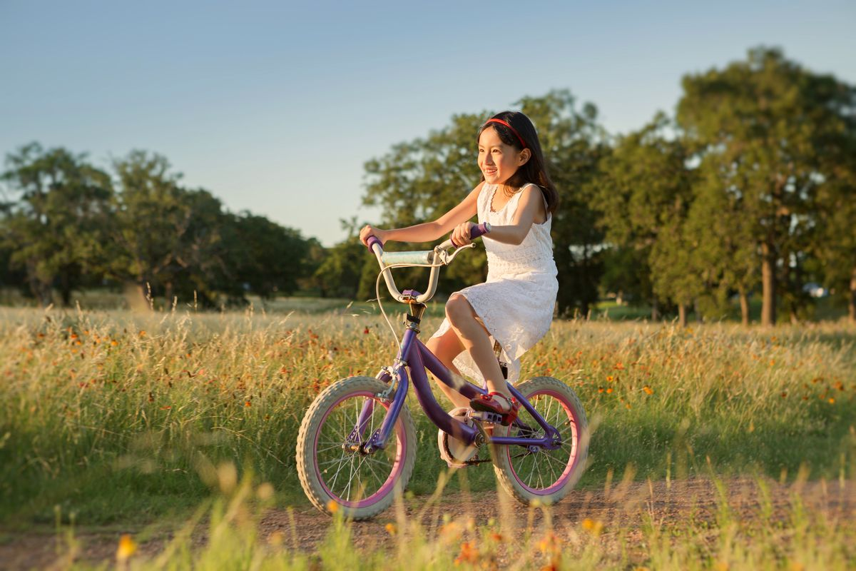 Smiling girl with light brown skin on a pink bike riding in a field.