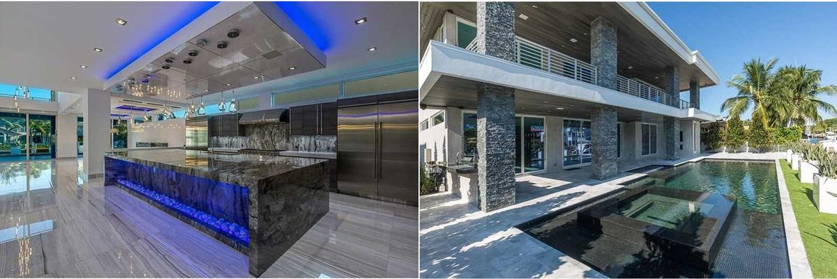 Inside the kitchen of a luxury waterfront home in Fort Lauderdale, with neon blue lighting on the side of the island, stone counterop, and open living area.