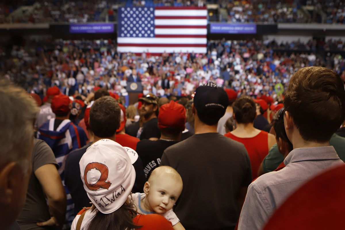 """17fa46fd3 Roxanne Kravitz, wearing a """"Q"""" hat with her son Indigo, listens to  President Donald J. Trump speak to a large crowd on August 2, 2018, at the  Mohegan Sun ..."""