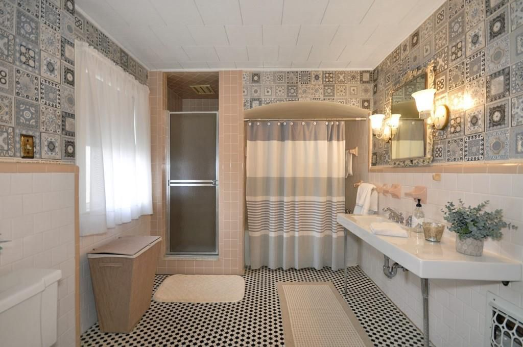 A bathroom with a tub and a shower stall.