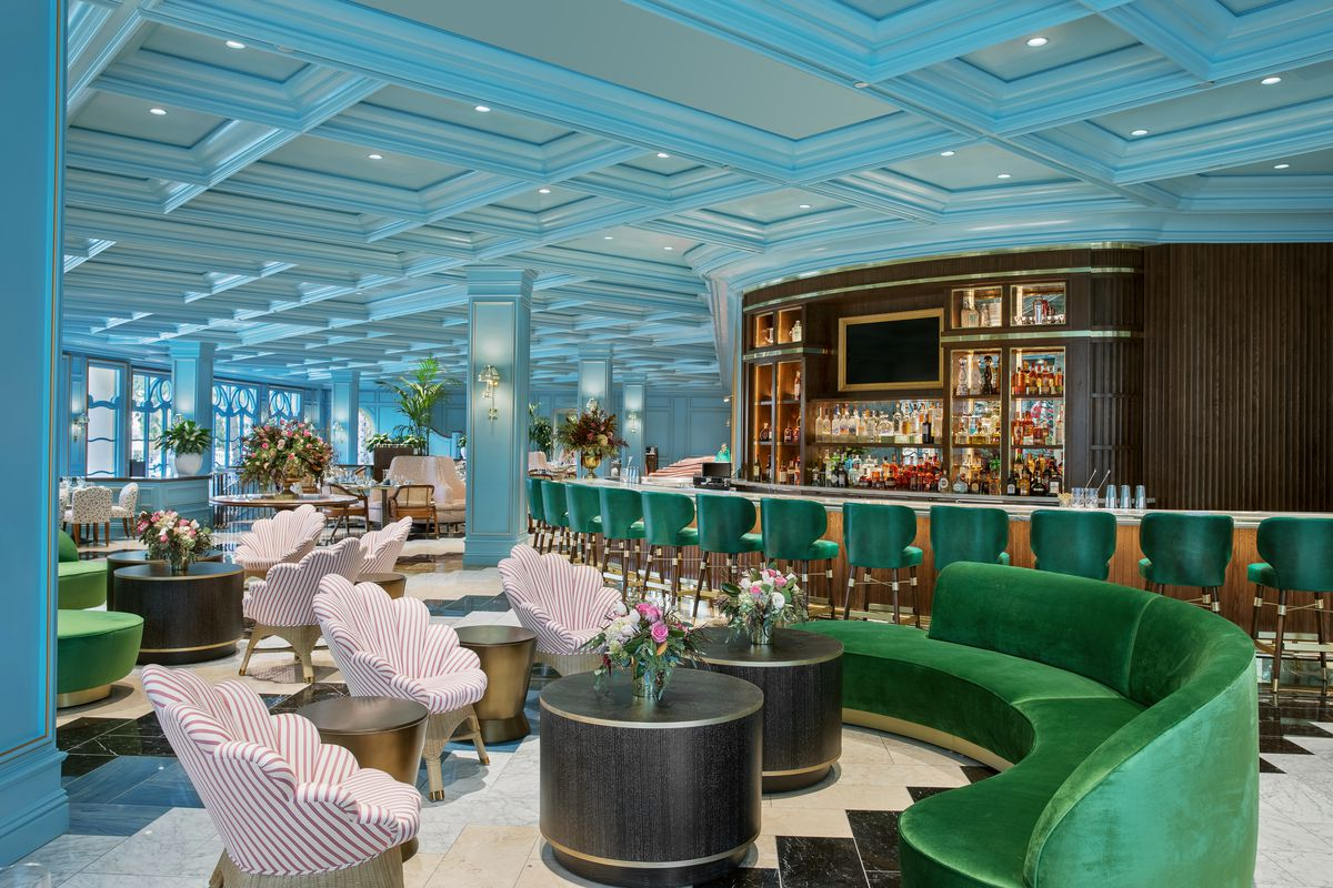The interior of Sadelle's has green velvet seating and sky blue walls.