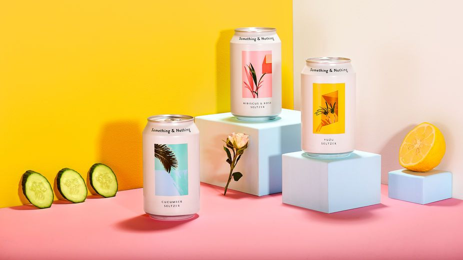 Three cans of yuzu; cucumber; and hibiscus and rose seltzer on turquoise plinths with a yellow and pink background