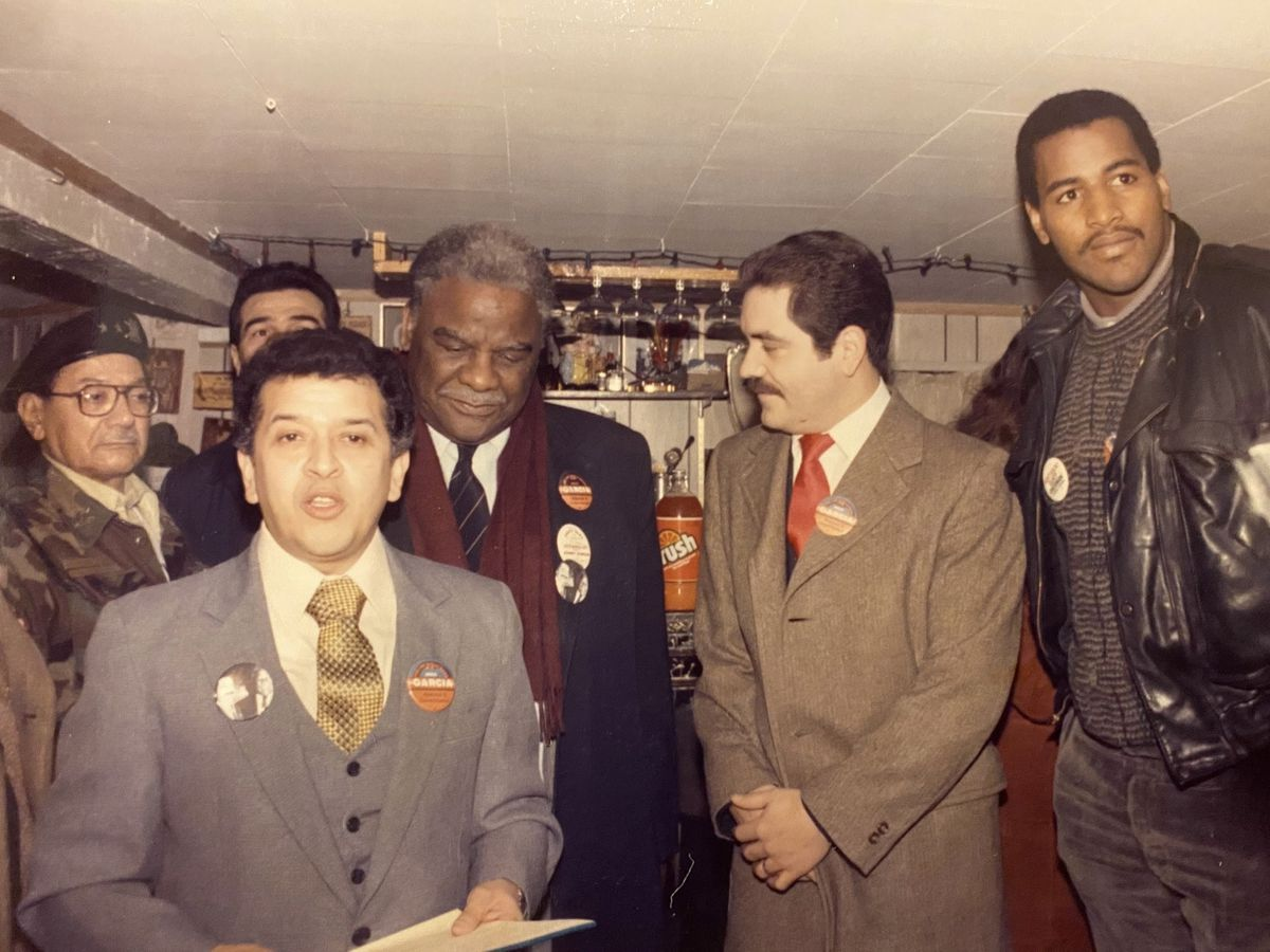 """Raúl Montes (foreground) with (to his left), former Mayor Harold Washington, U.S. Rep. Jesus """"Chuy"""" Garcia and Richard Dent, the Chicago Bears' Hall of Fame defensive end."""