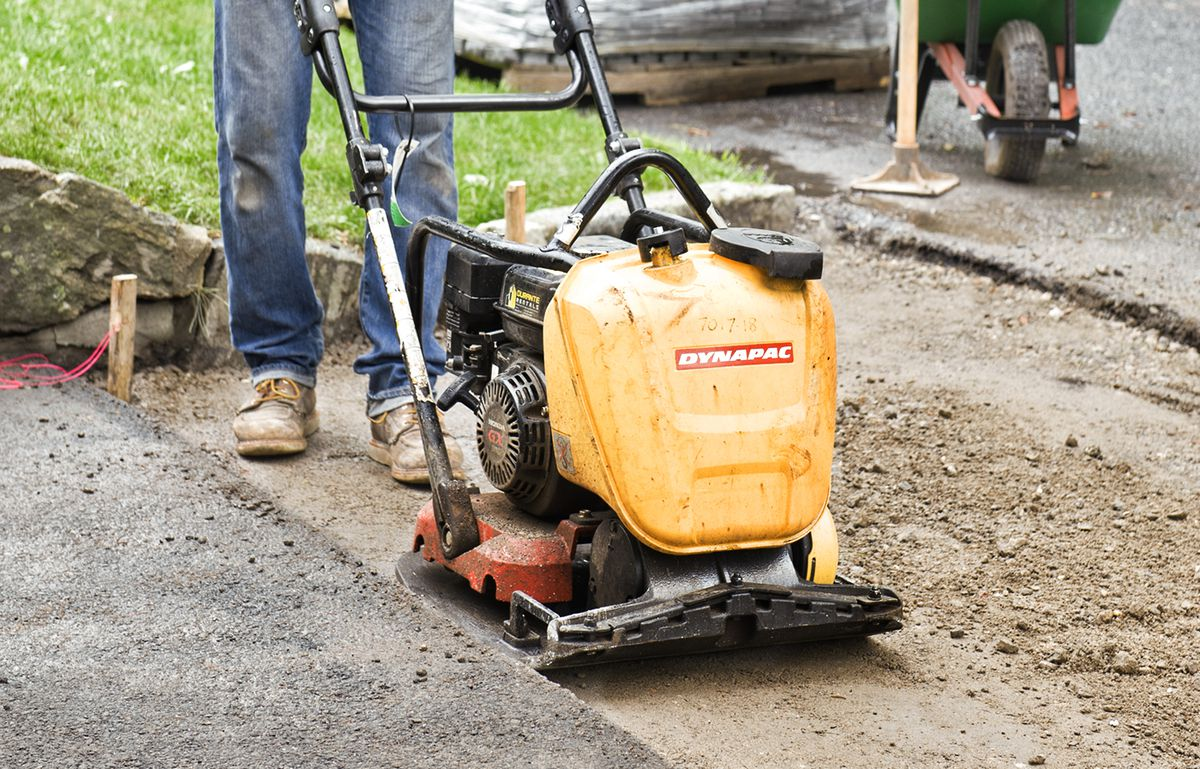 Man Packs Sand With Plate Compactor
