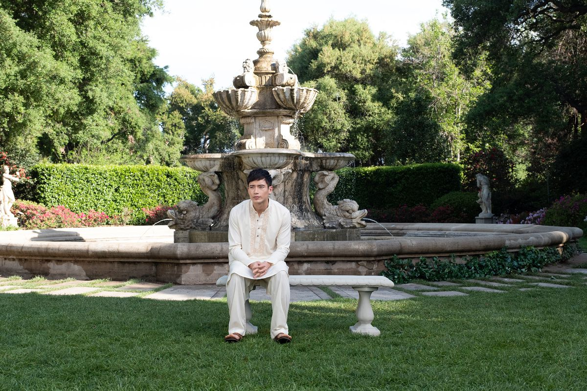 Jason sits pensively by a fountain.