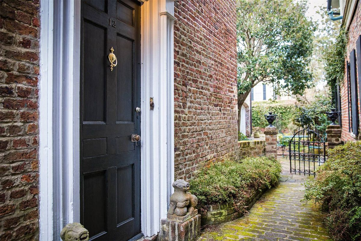 Close-up of front door of old brick house through alley.