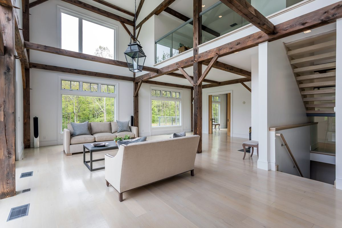 A living room has light pine floors, beige couches, exposed wooden beams and white walls.