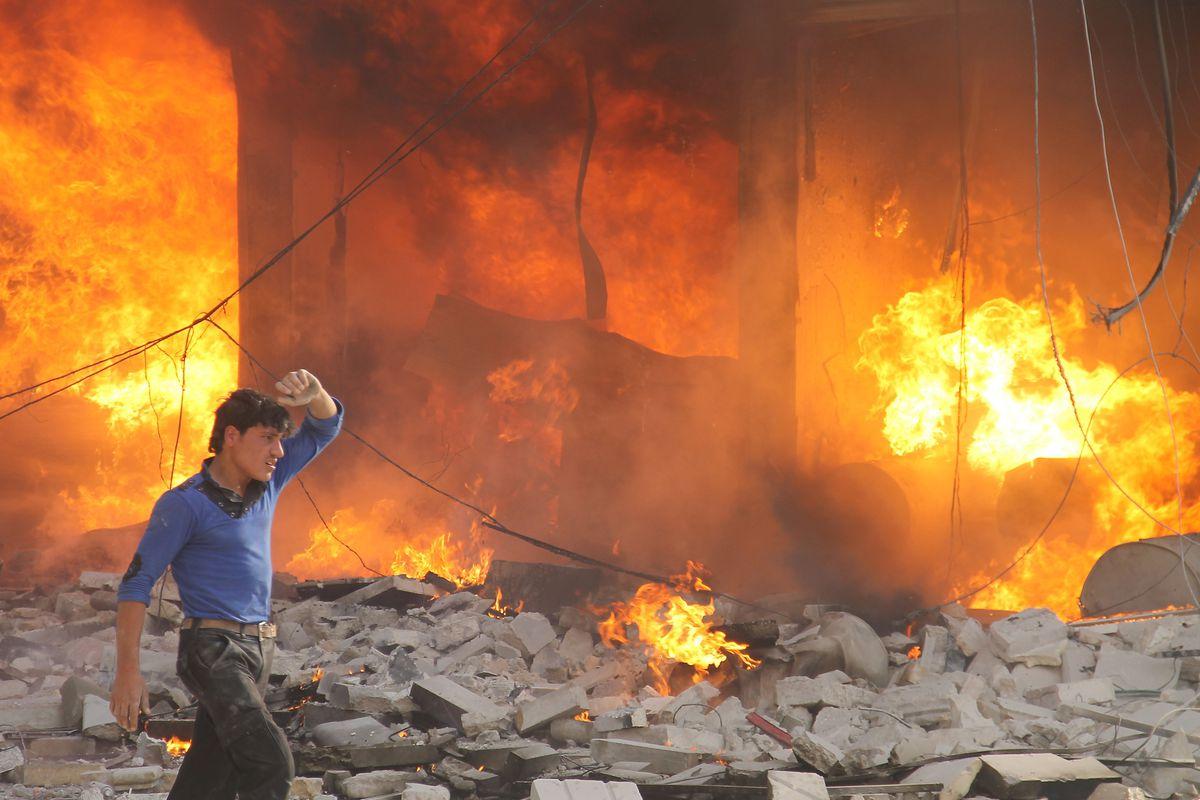 A Syrian man walks by a burning building in Aleppo, Syria.