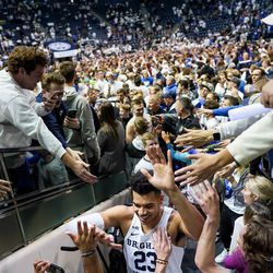 Brigham Young Cougars forward Yoeli Childs (23) celebrates with fans after BYU toppled No. 2-ranked Gonzaga 91-78 at the Marriott Center in Provo on Saturday, Feb. 22, 2020.