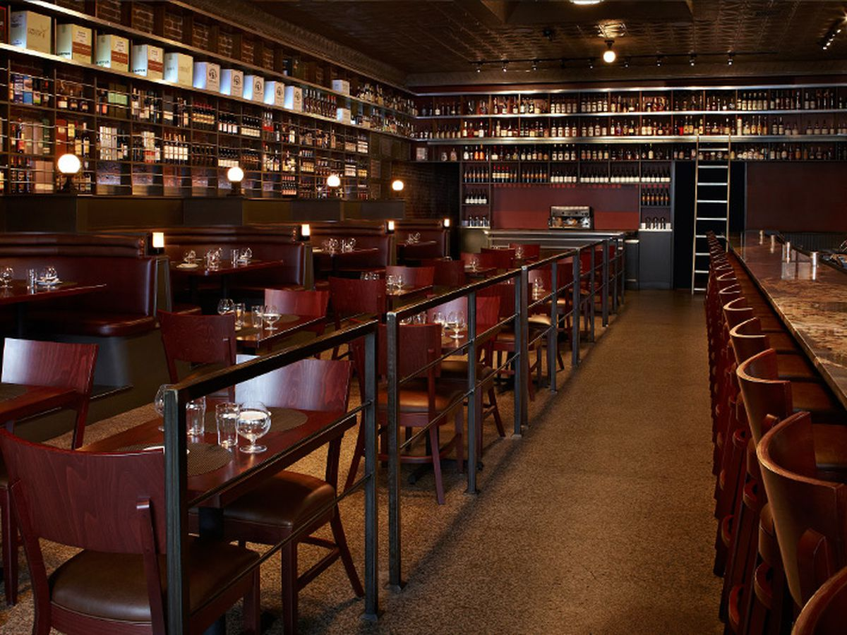 Three of Jack Rose's walls lined with bottles of whiskey, with wooden tables in the center.