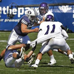 Brigham Young Cougars linebacker Uona Kaveinga (4) and Brigham Young Cougars defensive lineman Russell Tialavea (52) attack Weber State Wildcats quarterback Mike Hoke (11) behind scrimmage during the first half as Brigham Young University plays Weber State University in football  Saturday, Sept. 8, 2012, in Provo, Utah.