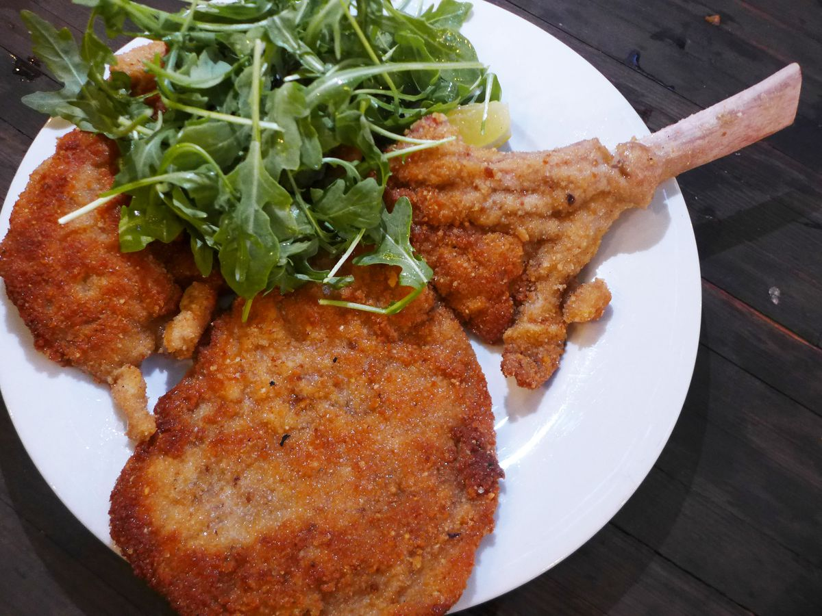 A hunk of veal is fried with the bone on and served beside a heap of arugula on a white plate